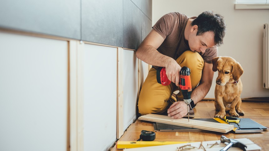 man using drill for home renovation project with dog