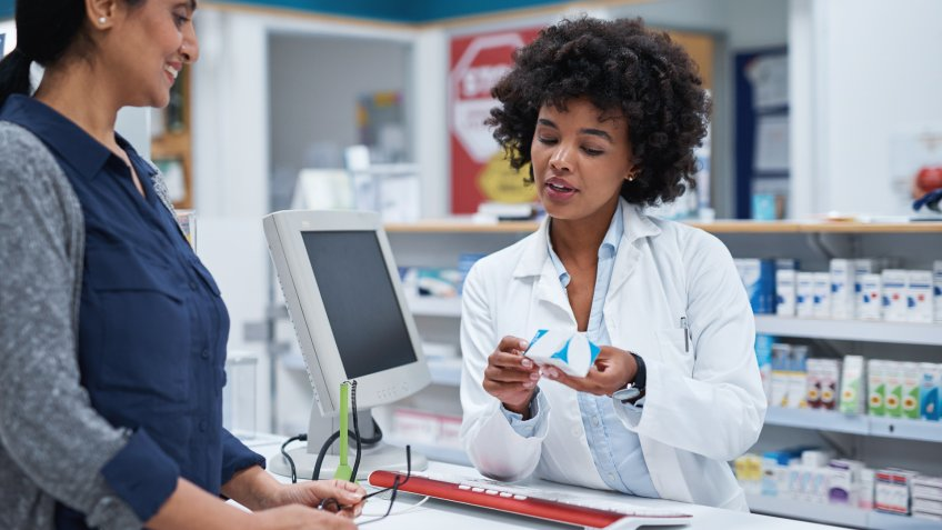 Shot of a pharmacist assisting a customer in a chemist.