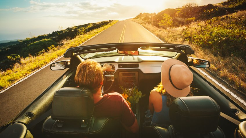 Happy Young Couple Driving Along Country Road in Convertible at Sunset - Image.