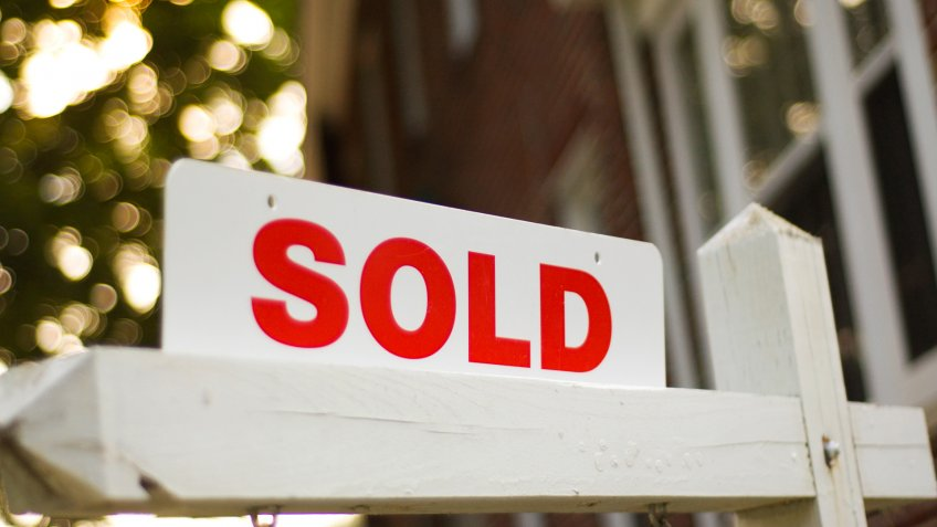 "Real Estate ""sold"" sign with red brick building and trees blurry in the background."