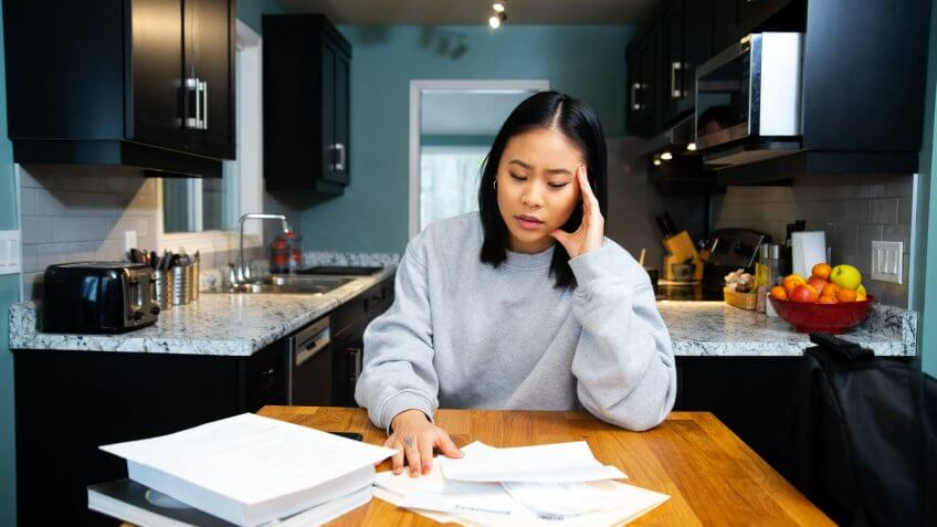 A female student worrying about financial issues at home in her apartment.