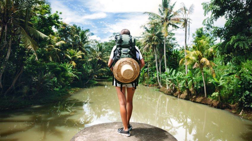 Woman with backpack standing on the edge near big tropical river and looking far away.