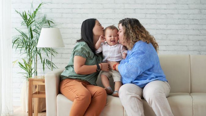 Mothers kissing their happy laughing child on both cheecks.