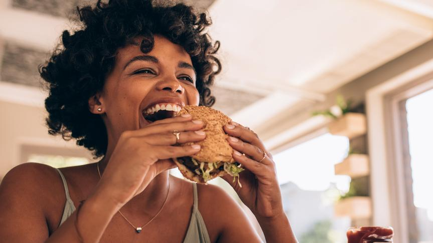 African woman eating stack burger at restaurawoman eating stack burger at restaurant with friends.nt with friends.