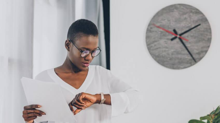 stylish african american businesswoman holding documents and checking time in office, clock on white wall.