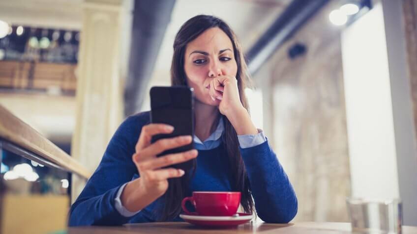 Young woman drink a cappuccino at the cafe, using mobile phone, texting.