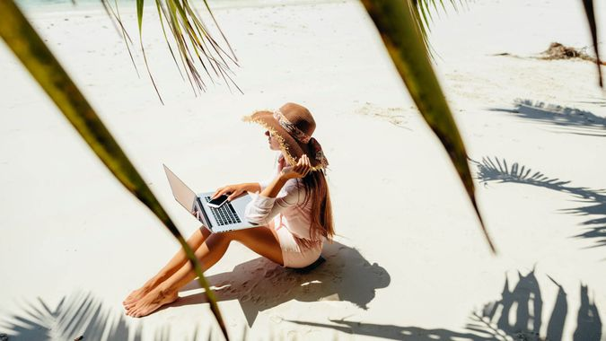 freelancer woman with laptop on beach.