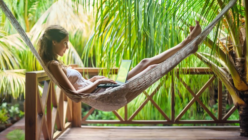 Young beautiful woman lying in a hammock with laptop in a tropical resort.