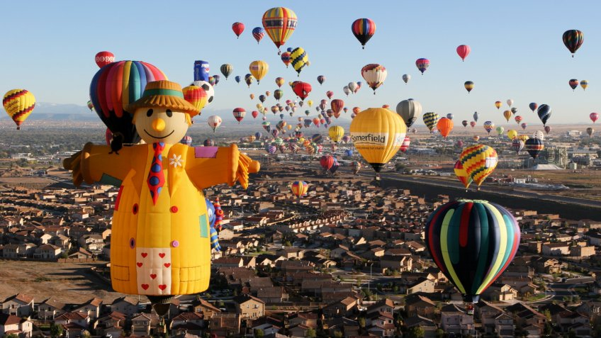 Albuquerque, New Mexico, USA - October 11, 2006: The scarecrow special shape hot air balloon ascends at dawn with hundreds of other balloons above Albuquerque at the Albuquerque International Balloon Fiesta - the largest such festival in the world.