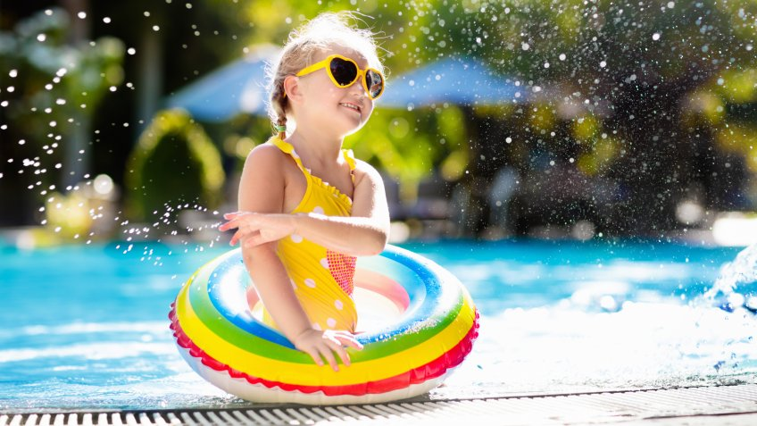 Child with goggles in swimming pool.