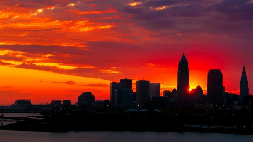The rising sun peeks out from behind nearly silhouetted buildings of downtown Cleveland Ohio.