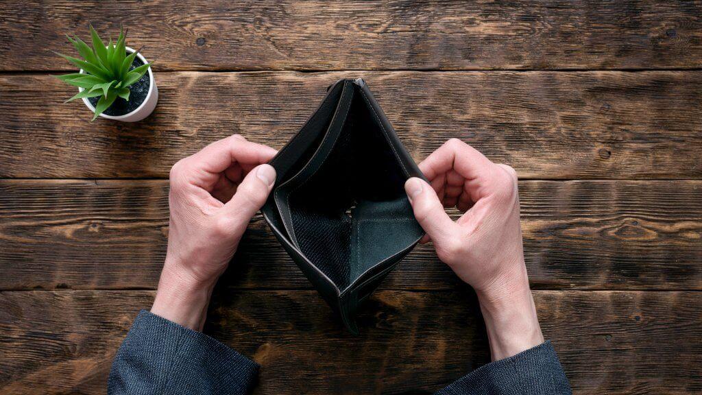 Empty wallet in hands on an office table shutterstock_1347772349