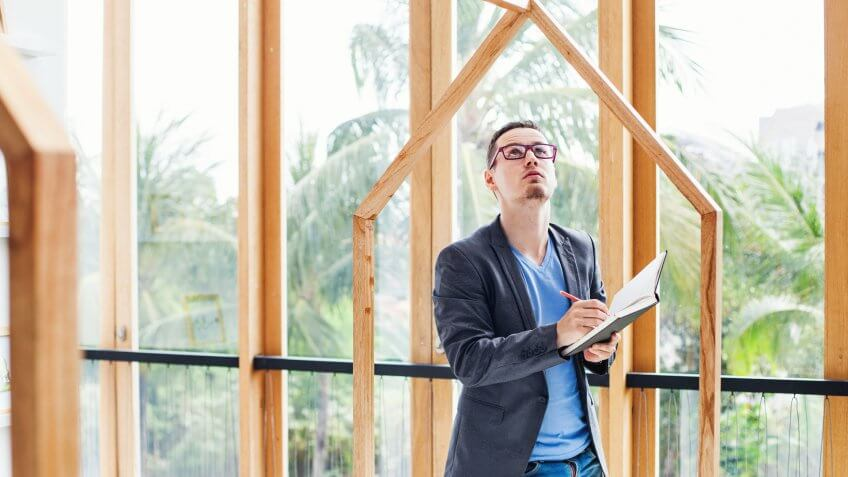 young engineer looking at a empty frames in a villa with tropical garden and writing something at his copybook.
