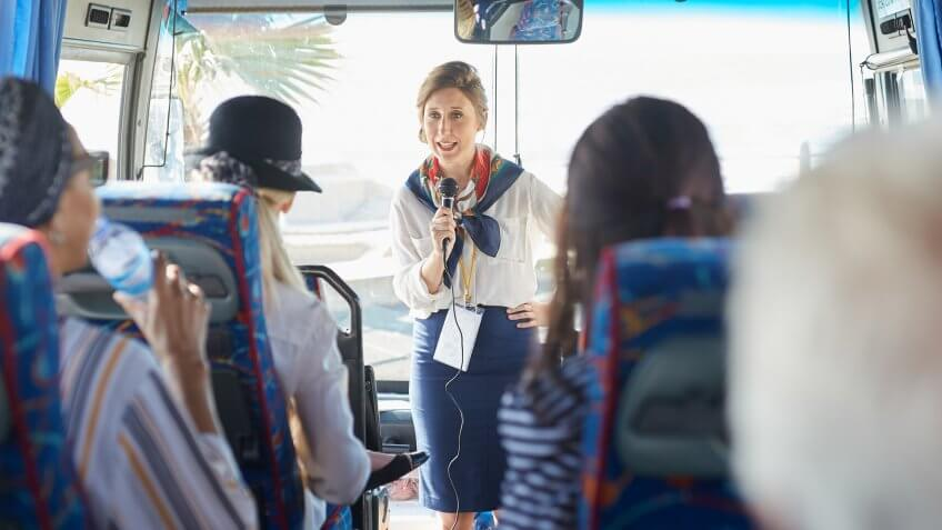 Female tour guide with microphone talking to active senior tourists on tour bus.