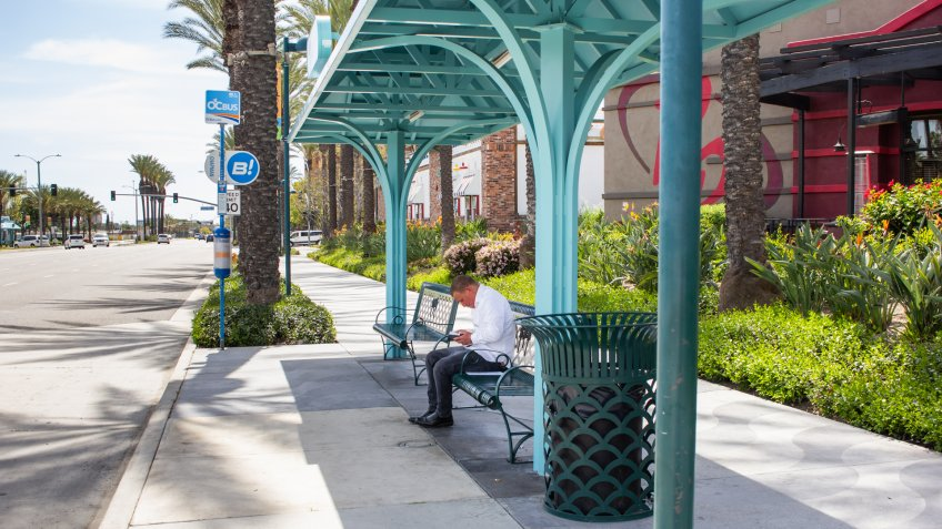Garden Grove, California/United States - 04/01/19: A man sits at a covered bus stop near the street.
