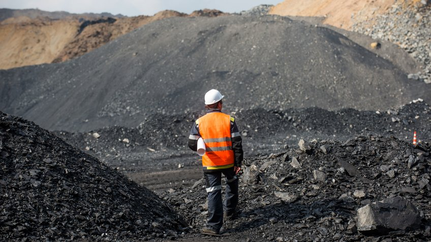 Coal mining in an open pit - Worker is looking on the huge open pit.