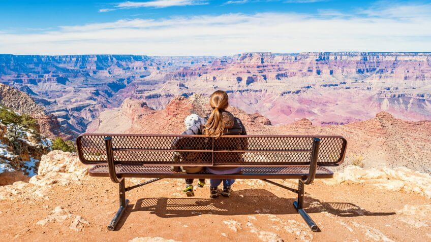 Stock photograph of a mother with child looking at view in Grand Canyon National Park, South Rim, USA on a sunny day.