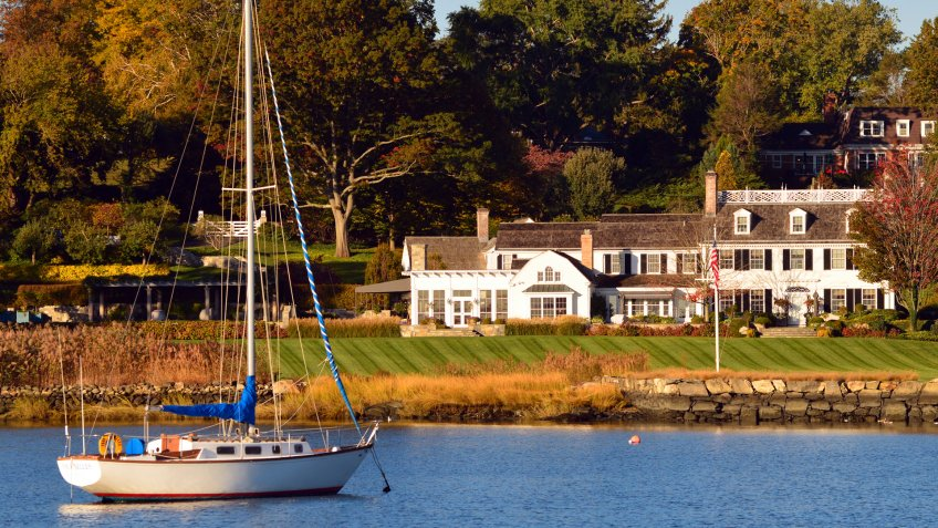 Greenwich, CT, USA October 27, 2013 A sailboat is moored just off shore of a Luxury Waterfront Home in Greenwich, Connecticut.