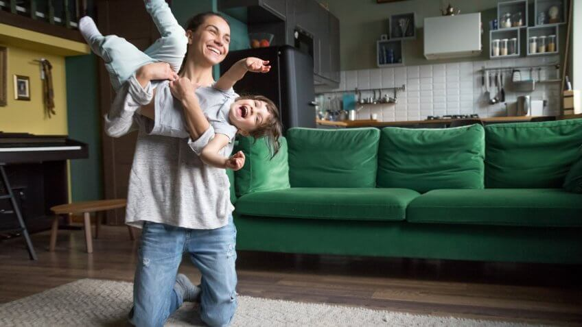 Excited mother holding lifting kid daughter flying laughing on weekend, young family single mom or babysitter nanny playing with active cute girl at home, happy mommy and child having fun together.