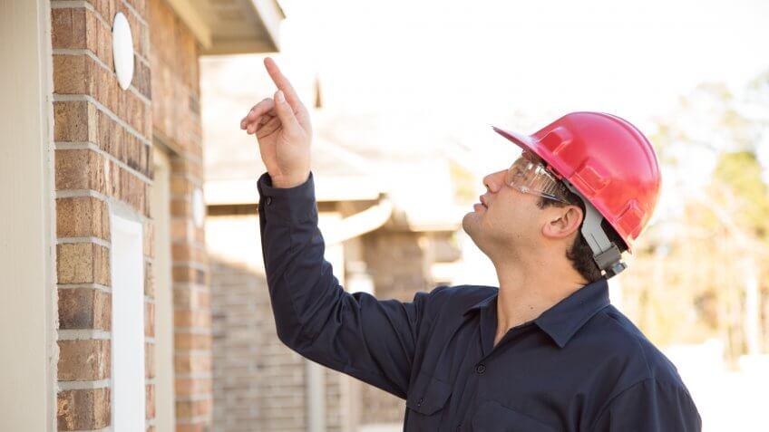 Latin descent home inspector, engineer, insurance adjuster, exterminator, or repairman examines recent house construction using his digital tablet.