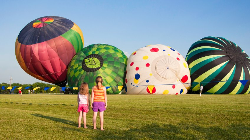 Four hot air balloons rise up into the blue sky at a festival in rural Kansas while two young girls watch from the grass - Image.