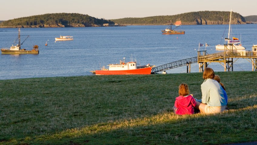 """""""Family watches harbor scenes as suns sets in Bar Harbor, Maine."""