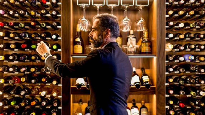 Middle-aged handsome man chooses a bottle of wine.