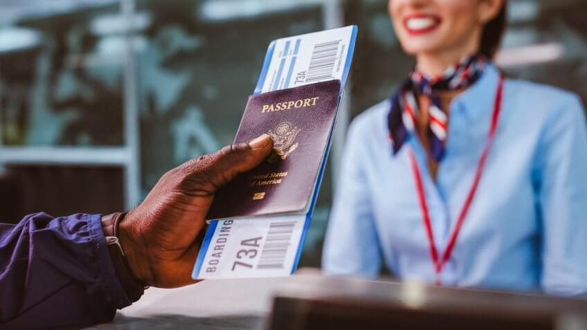 African American man holding boarding pass and passport at airline check-in desk at international airport.