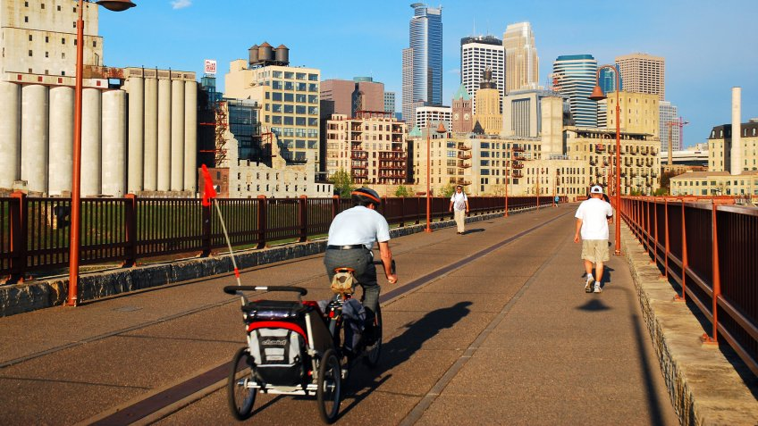 Minneapolis, MN, USA May 14, 2013 An adult man commutes to work, carrying his child in a bicycle trailer, crossing the Stone Arch Bridge in Minneapolis, Minnesota - Image.