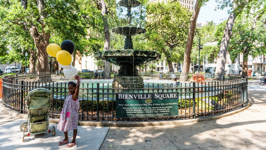 Mobile, USA - April 22, 2018: Old town Bienville square fountain in park by street in Alabama famous southern town, city, young african american girl with balloons.