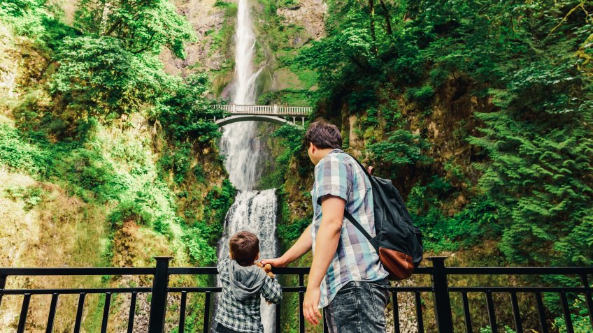 Father and his small son looking on Multnomah Falls waterfall along the Columbia River Gorge, Oregon, USA.