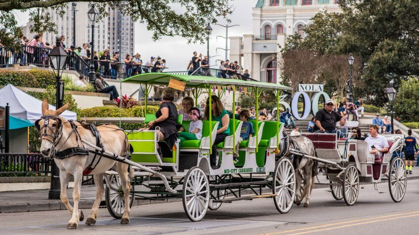 New Orleans, Louisiana / USA - February 17, 2019: A family enjoys a horse drawn carriage ride through Jackson Square in the French Quarter.