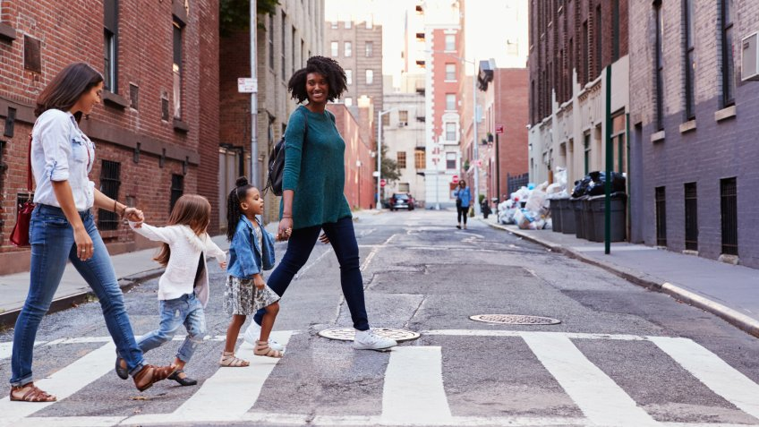 Two mother friends with two daughters crossing the road.