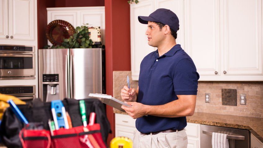 Hispanic repairman or blue collar/service industry worker makes service/house call inside customer's home kitchen.