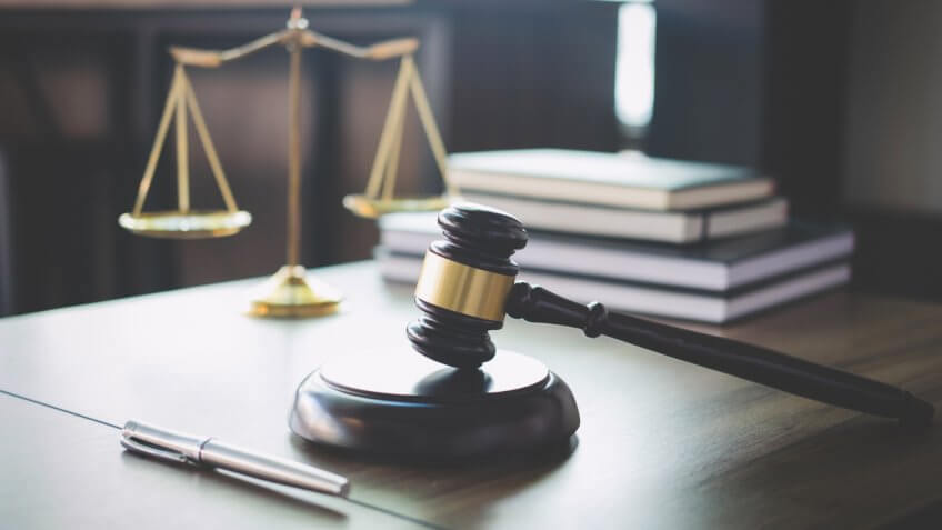 Scales of justice and Gavel on wooden table and Lawyer or Judge working with agreement in Courtroom, Justice and Law concept.