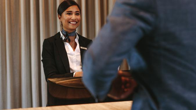 Smiling hotel receptionist talking with male guest at reception counter.