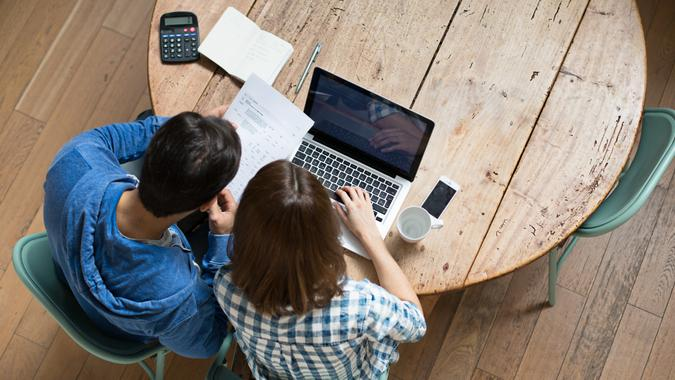 Elevated view from a young couple checking their home finances at home.