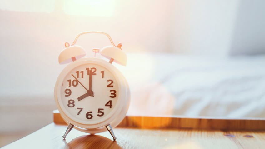 morning time background, alarm clock near the bed at home.