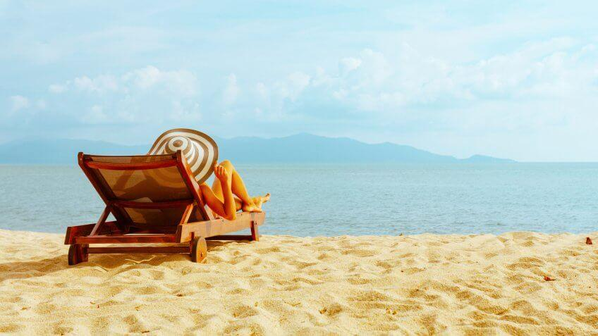 woman sunbathing in beach chair with outstretched arms on the beach.