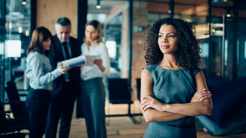 Beautiful african-american ethnicity woman sitting confidently in office looking away.