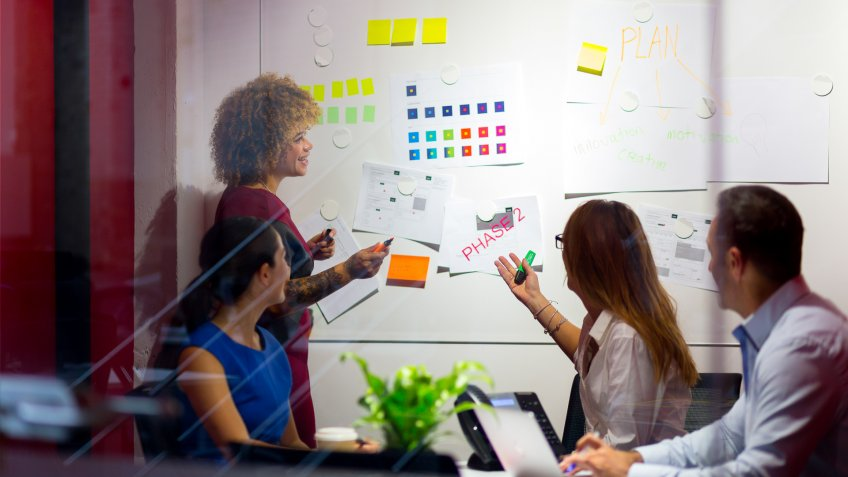 Business woman listening to ideas from other members sitting looking at the whiteboard in front of them.