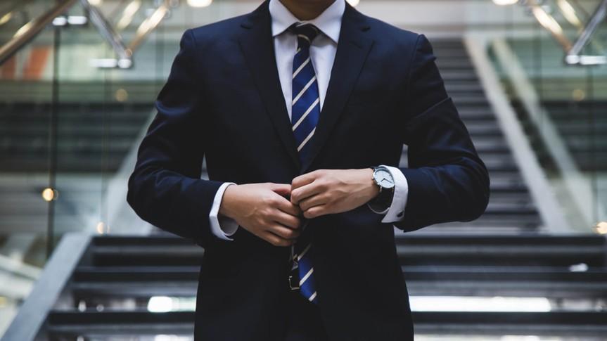 businessman buttoning up his suit jacket