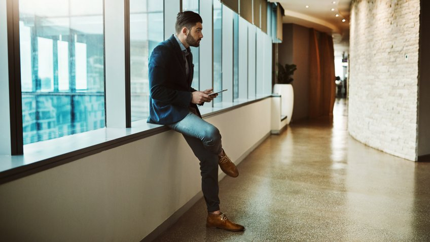 Shot of a young businessman looking thoughtful while using a digital tablet in a modern office.