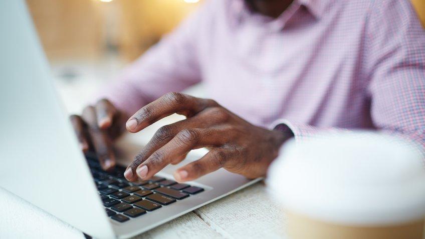 Hands of businessman or designer typing on l aptop.