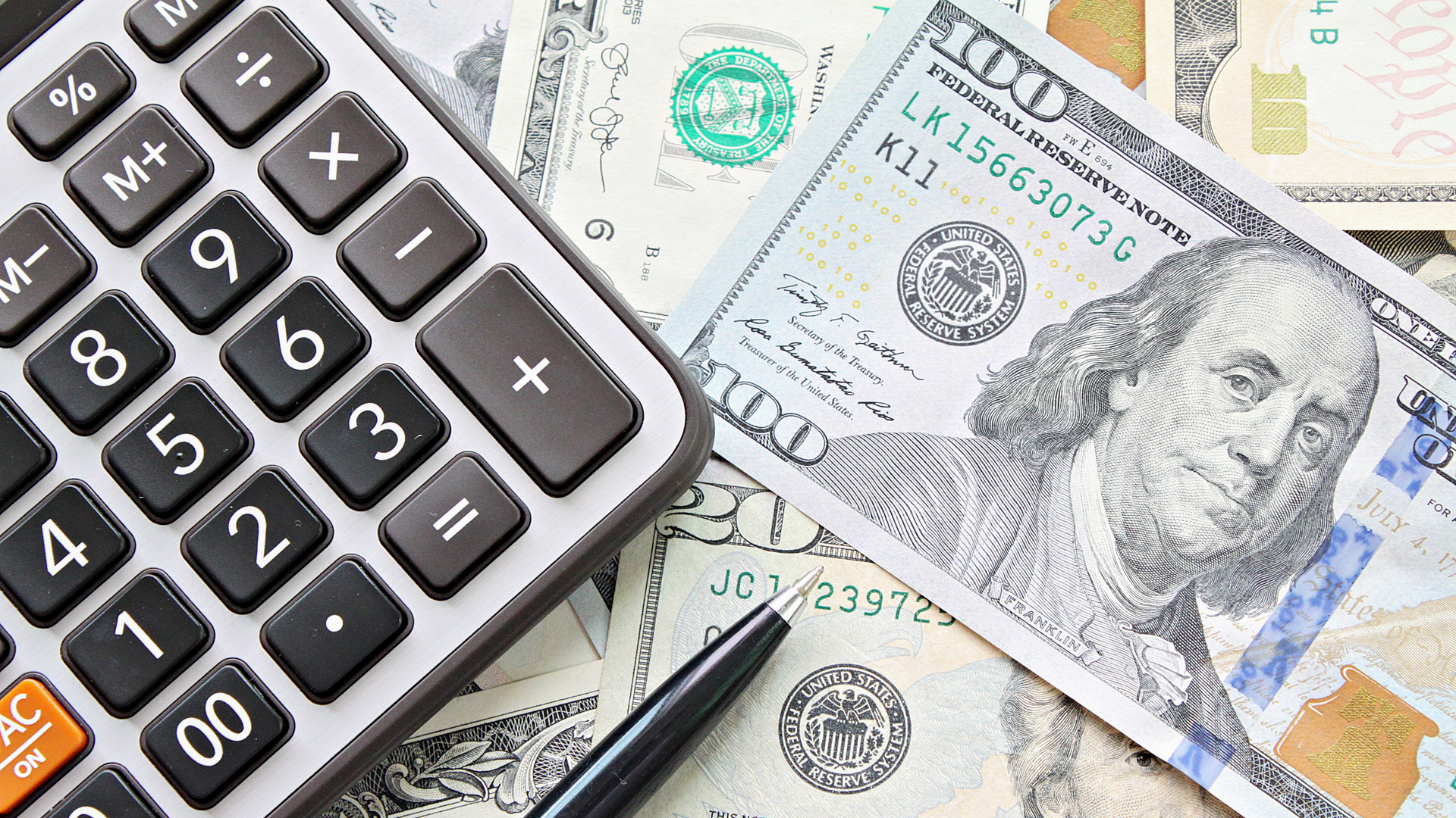 Business, finance, investment, accounting, taxes or money exchange concept : Top view or flat lay of calculator and pen on American Dollars cash money.