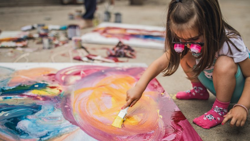 Little girl painting outdoors.