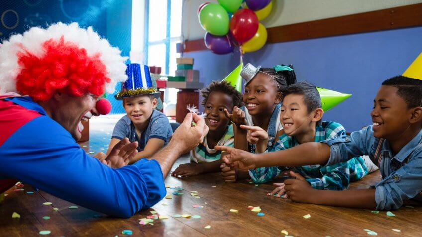 Clown showing feather to children sitting at desk during birthday.