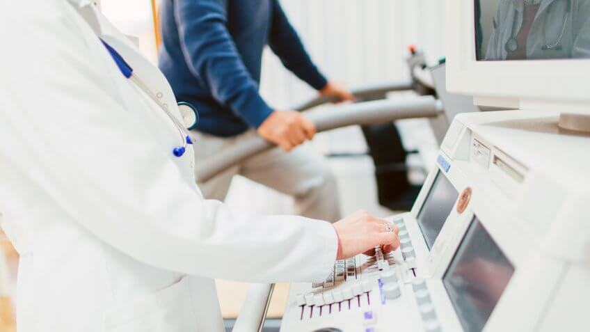 Senior patient is being measured by a doctor for a stress test on a treadmill.
