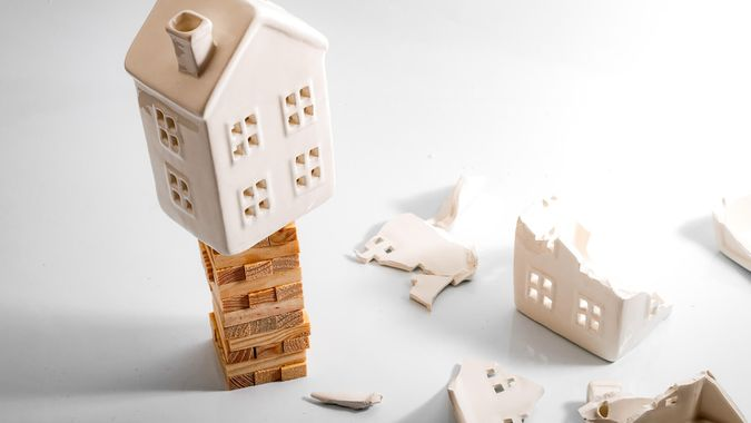 Financial risk, unstable real estate investment and shaky housing market concept with a home on stacked wooden building blocks surrounded by the ruins and debris of another house that collapsed.
