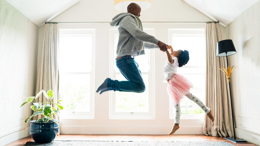 Side view of father and daughter jumping while performing ballet.
